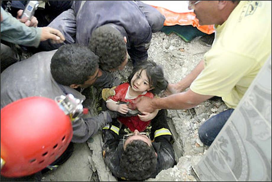 Emilie Kaidi, 2, emerges from the rubble of her home in Corso, Algeria, yesterday in the hands of a rescue worker, two days after a quake hit in the region, killing more than 1,400 and wounding over 7,000. Photo: / Associated Press