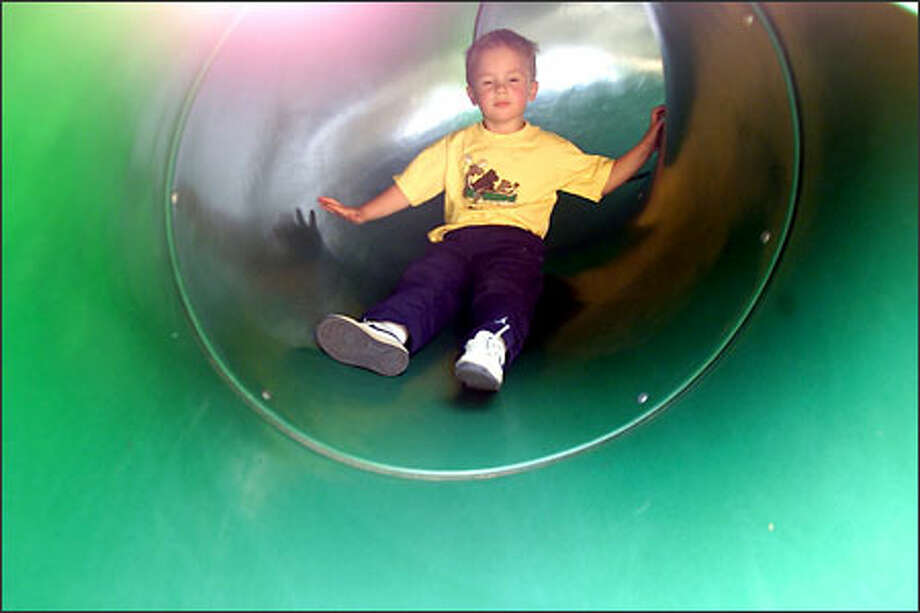 Wheeeee, here I come ... 3-year-old Keller Brown of Bothell takes a ride down a circular slide at the new playground at St. Edward State Park in Kenmore. Photo: Loren Callahan/Seattle Post-Intelligencer