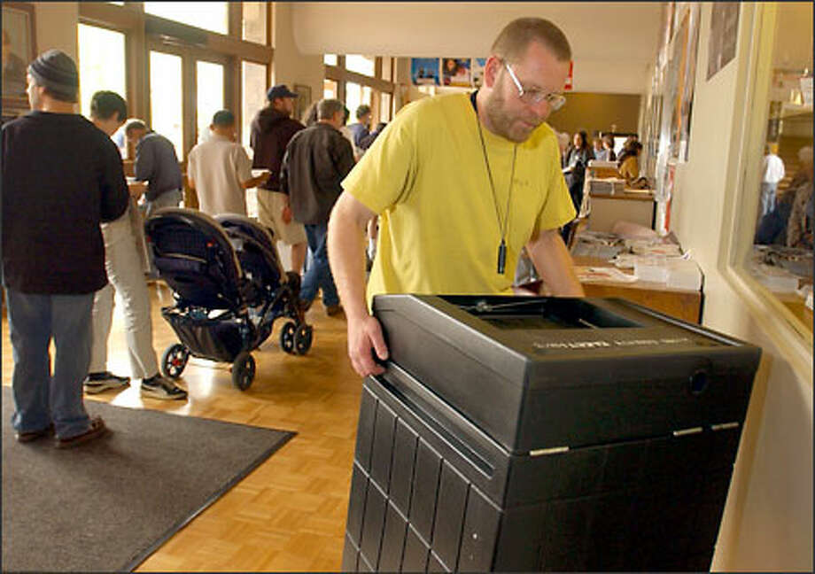 Larry Price, a technician at the Seattle International Film Festival, shakes a King County ballot box he found in the lobby of the Broadway Performance Hall. Photo: Ron Wurzer/Seattle Post-Intelligencer