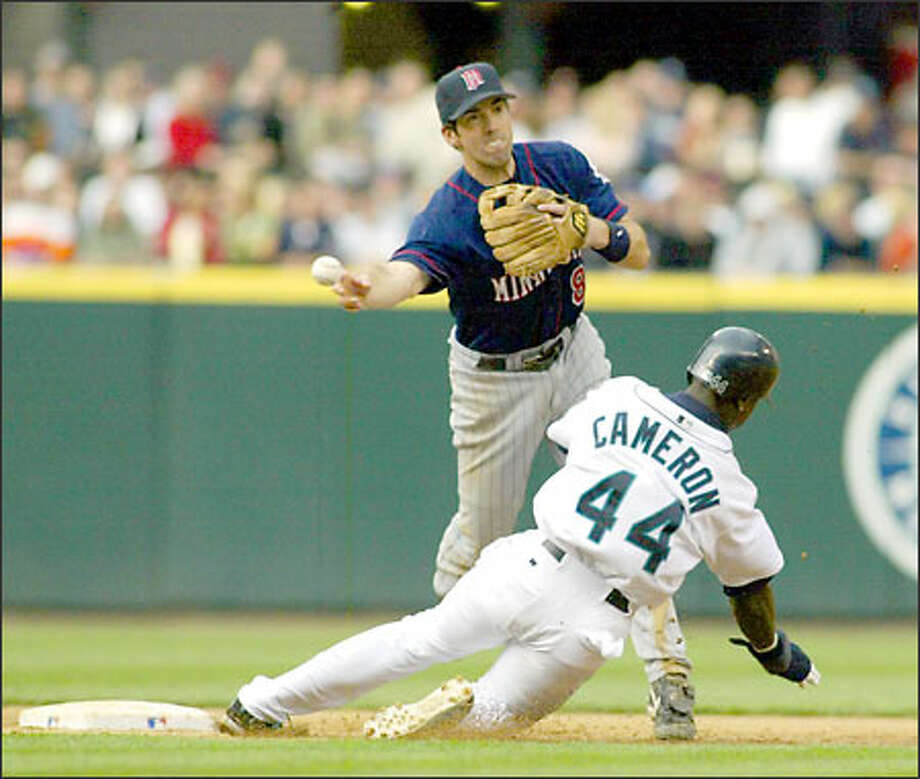 Mike Cameron breaks up a double play attempt by Minnesota's second baseman Chris Gomez in the fifth inning. Photo: Jim Bryant/Seattle Post-Intelligencer