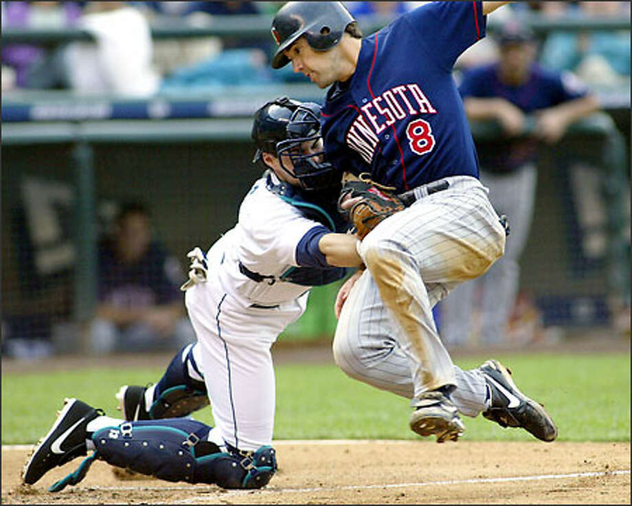 Mariners catcher Ben Davis tags out Twins baserunner Chris Gomez during the fifth inning yesterday at Safeco Field. Ichiro made the throw from right to nail Gomez. Photo: TED S. WARREN/AP