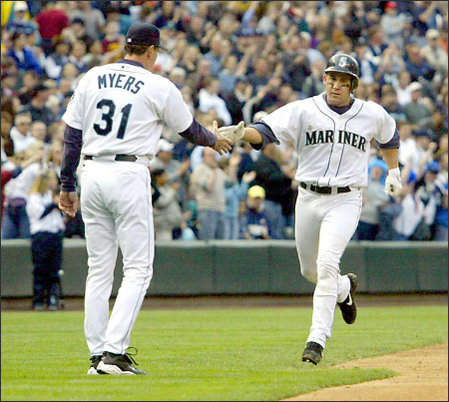 Bret Boone is congratulated by third base coach Dave Myers after hitting a solo home in the seventh inning. Photo: Jim Bryant/Seattle Post-Intelligencer
