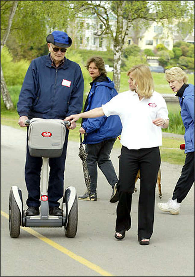 Dale Blanchard of Redmond tries out a Segway with help from Sara Powers, whose company will rent the scooters. Photo: Meryl Schenker/Seattle Post-Intelligencer