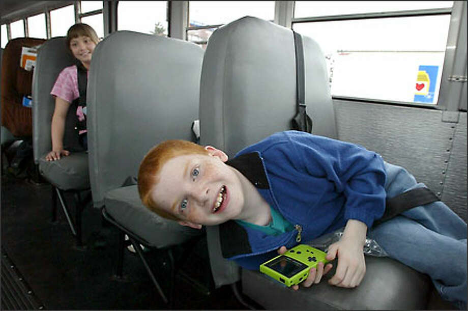 """Scott Brown and Alexias Davis are learning focus and discipline even on the school bus with a Books on Wheels program. """"It entertains me,"""" Davis said. Photo: Gilbert W. Arias/Seattle Post-Intelligencer"""