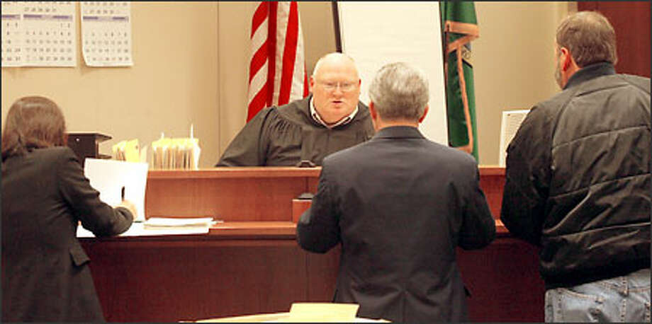 King County District Court Judge Darrell Phillipson listens to a prosecutor, left, a defense attorney and client as a domestic violence trial date is scheduled. Phillipson presides over a King County domestic violence court in Kent. Photo: Grant M. Haller/Seattle Post-Intelligencer