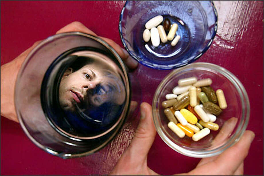 Frey Allyn, 34, a graphics student at Shoreline Community College, takes more than 40 vitamins each day, the clear cup in the morning, the other cup at night. Photo: Mike Urban/Seattle Post-Intelligencer