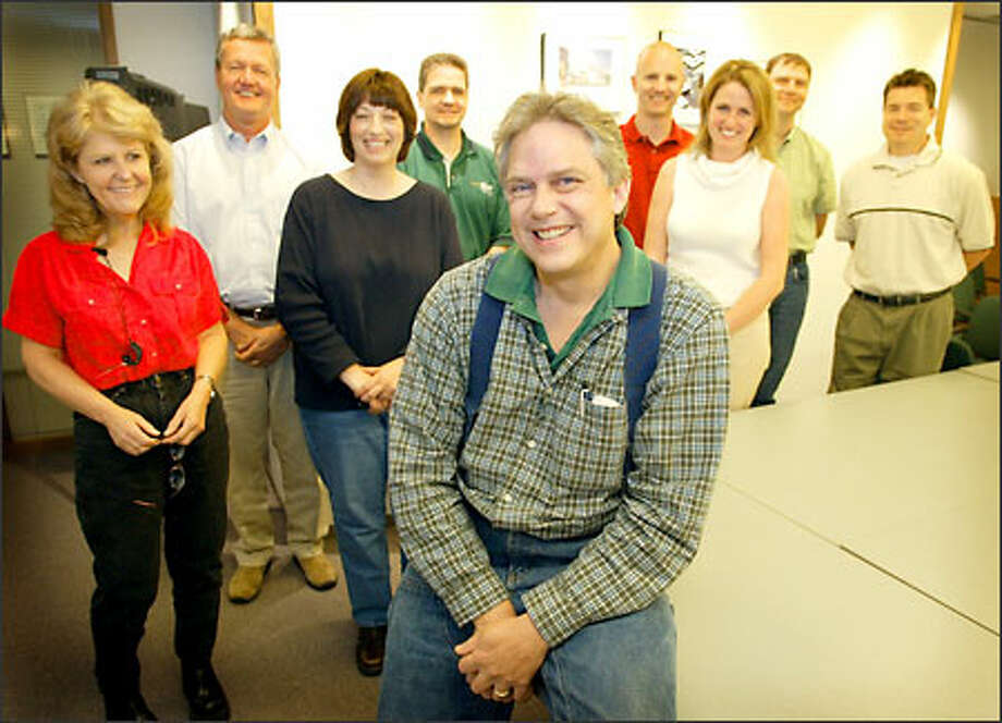 Dennis Richter, center, with colleagues at Valley Electric in Bothell. Co-workers collected $22,000 to pay for Richter's cancer treatment in Germany. Photo: Gilbert W. Arias/Seattle Post-Intelligencer