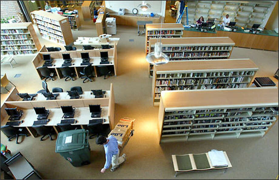 Inside the new Capitol Hill branch library, a worker put on a few finishing touches yesterday as the library gets set to open with a celebration today at noon. Photo: Gilbert W. Arias/Seattle Post-Intelligencer
