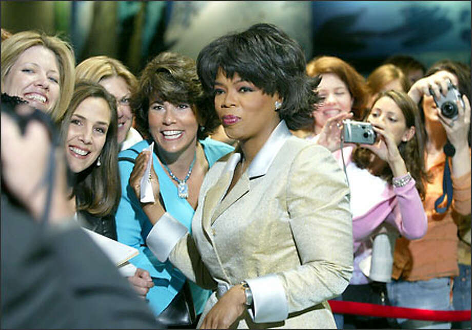"""Fans have their pictures taken with Oprah Winfrey before the """"Live Your Best Life"""" workshop at the Washington State Convention and Trade Center. Photo: Meryl Schenker/Seattle Post-Intelligencer"""