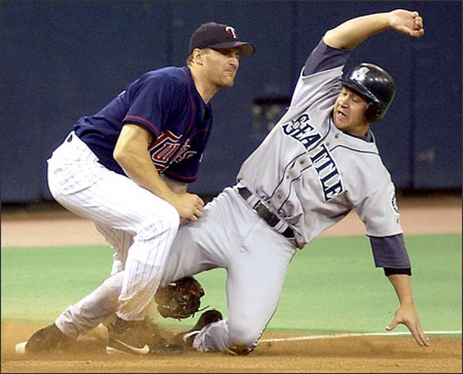 Bret Boone slides safely into third base ahead of the throw to Minnesota's Corey Koskie during the first inning. Boone scored on Mike Cameron's single. Photo: CRAIG LASSIG/AP