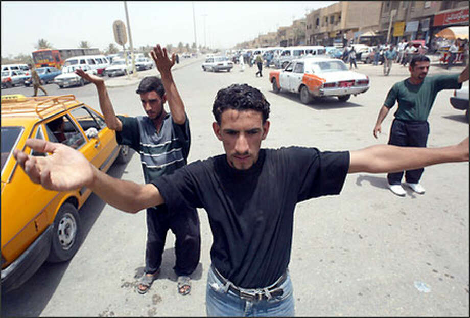Young Iraqis such as Luay Abid Zbar, center, direct traffic at the busy Al Baya'a intersection in central Baghdad. Volunteers like these young men have taken to the streets to try to unsnarl some of the transportation chaos created by the absence of police and working traffic lights since the war. It is dangerous work. Photo: Dan DeLong/Seattle Post-Intelligencer