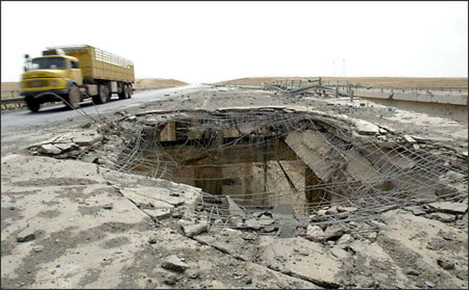 This section of the highway was severely damaged by U.S. bombing, requiring eastbound traffic to cross the median and drive in the west-bound lanes for a quarter-mile stretch. Photo: Dan DeLong/Seattle Post-Intelligencer
