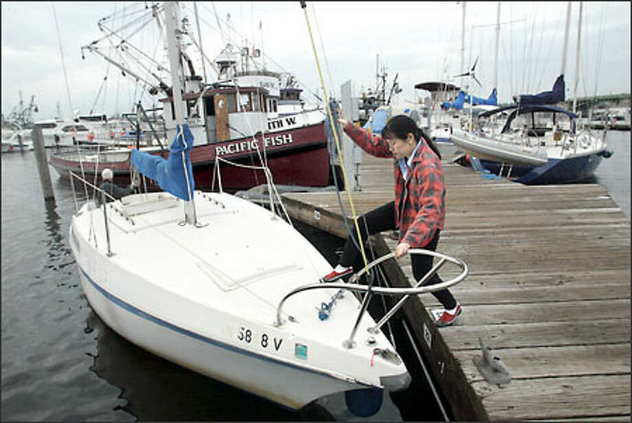May Leong climbs aboard the sailboat she shares with Rory Lysaght at Fishermen's Terminal. The Seattle residents say everyone's been very friendly on the dock. Photo: Karen Ducey/Seattle Post-Intelligencer