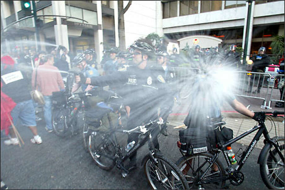 Police spray pepper spray into a crowd during a demonstration last night outside the Red Lion Hotel, site of a police intelligence-training seminar. Photo: Mike Urban/Seattle Post-Intelligencer