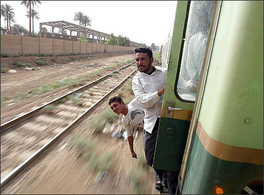 Fourteen-year-old Moustafa Al-Timimi, wearing a Kurt Cobain shirt, and Hussan Al-Hussani hang outside a rail car as the train to Basra leaves Baghdad. Photo: Dan DeLong/Seattle Post-Intelligencer