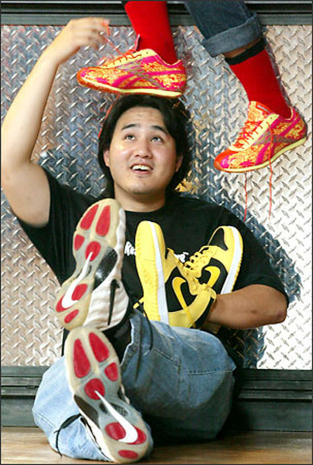 Mark Shin with sneakers from his collection: orange-and-yellow Reebok Gold Medalists, yellow Nike Dunk NYCs and, on his feet, Nike Air Foamposites. Photo: Mike Urban/Seattle Post-Intelligencer