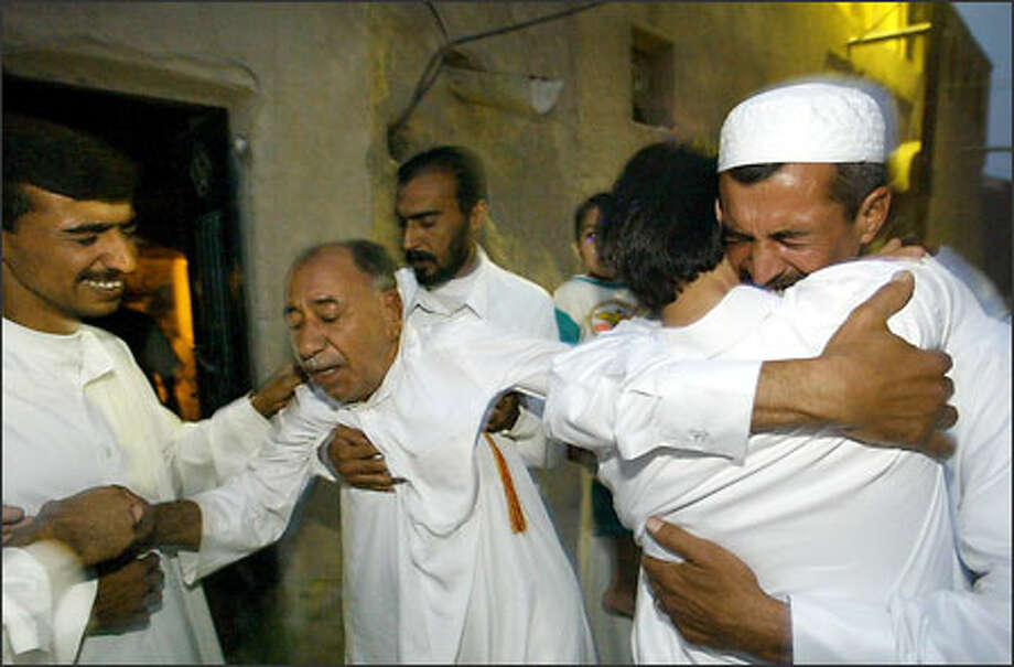 Mohammed Al-Tanini, 80, is overcome with emotion as his son Yahya Al-Garib arrives from Seattle. The two had not seen each other in 12 years. Yahya's brother Amar, left, and friend Saad help Mohammed as Yahya, back to camera, is embraced by his brother Rasam. Other family members wait their turn to give him a welcome-home hug. Photo: DAN DELONG/P-I PHOTO