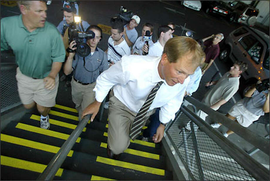 Rick NeuheiselUniversity of Washington football coach Rick Neuheisel, flanked by members of the news media, makes his way to the Don James Center for a team meeting. Photo: Gilbert W. Arias/Seattle Post-Intelligencer