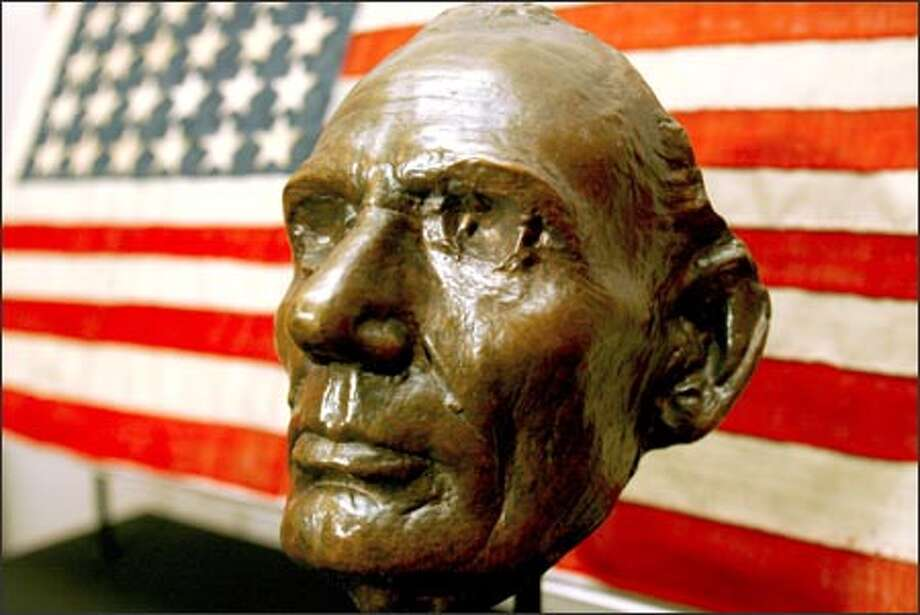 "A bronze life mask of Abraham Lincoln from 1860 is displayed in front of the American flag that flew from the president's funeral train. ""The American Presidency: A Glorious Burden,"" a touring Smithsonian Institution exhibition featuring more than 350 presidential artifacts, makes its only West Coast stop at the Museum of History and Industry. Photo: Grant M. Haller/Seattle Post-Intelligencer"