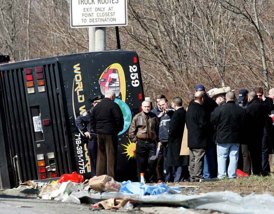 New York Police Commissioner Raymond Kelly speaks with emergency personnel investigating the scene of a bus crash on Interstate-95 in the Bronx borough of New York Saturday, March 12, 2011. At least thirteen people died when the bus, returning to New York from a casino in Connecticut, flipped onto its side and was sliced in half by the support pole for a large sign. (AP Photo/David Karp) Photo: DAVID KARP