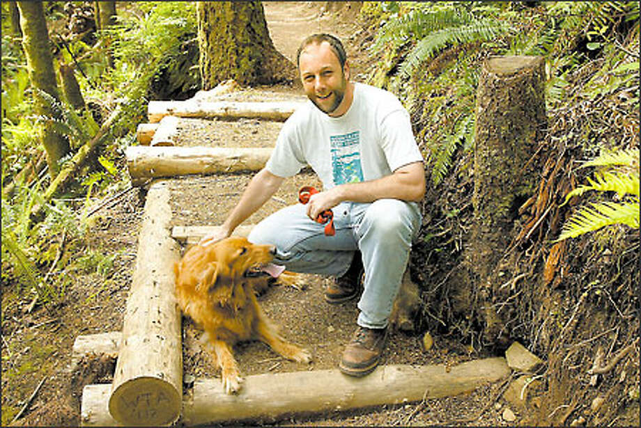 Doug Schindler, the director of field programs for the Greenway Trust, hangs out with pooch Casey on the Rattlesnake Ledge Trail. Photo: Meryl Schenker/Seattle Post-Intelligencer
