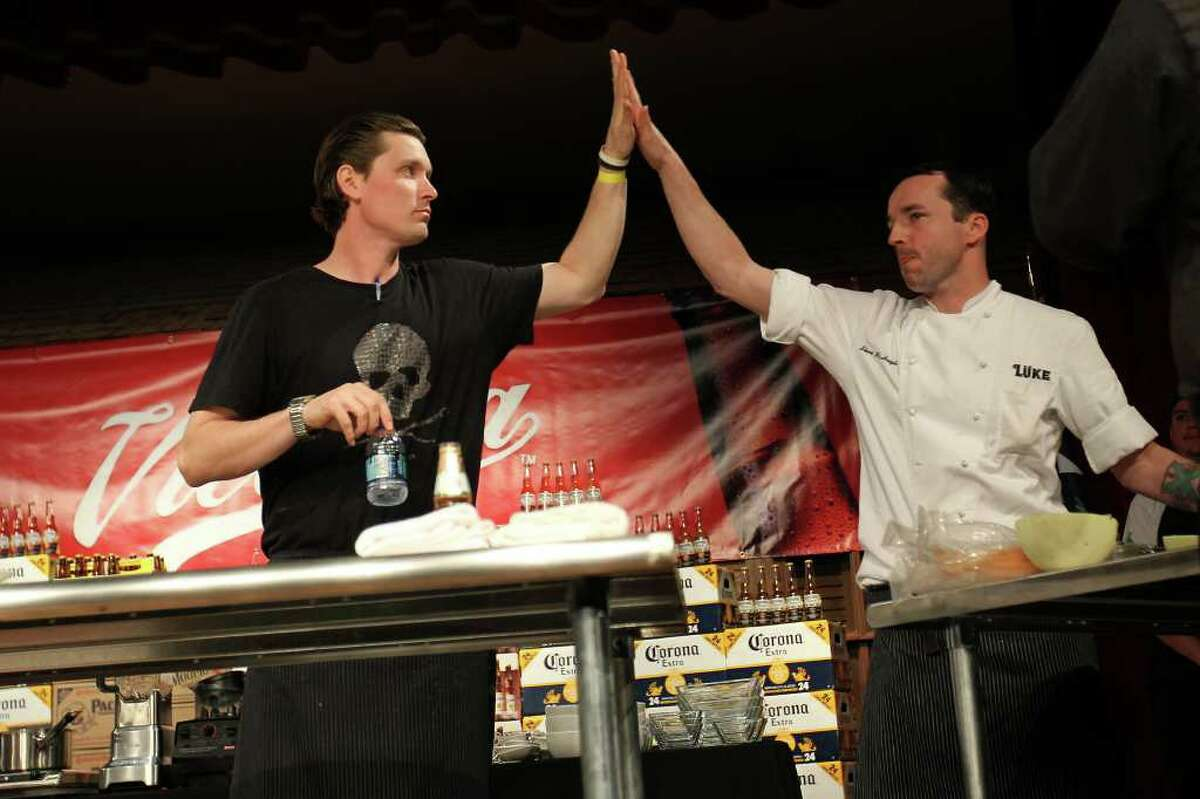 Chefs Jason Dady and Steven McHugh high-five after time is called in the Ceviche Challenge at the Paella Challenge at the Pearl Brewery, on Sunday, March 13, 2011.