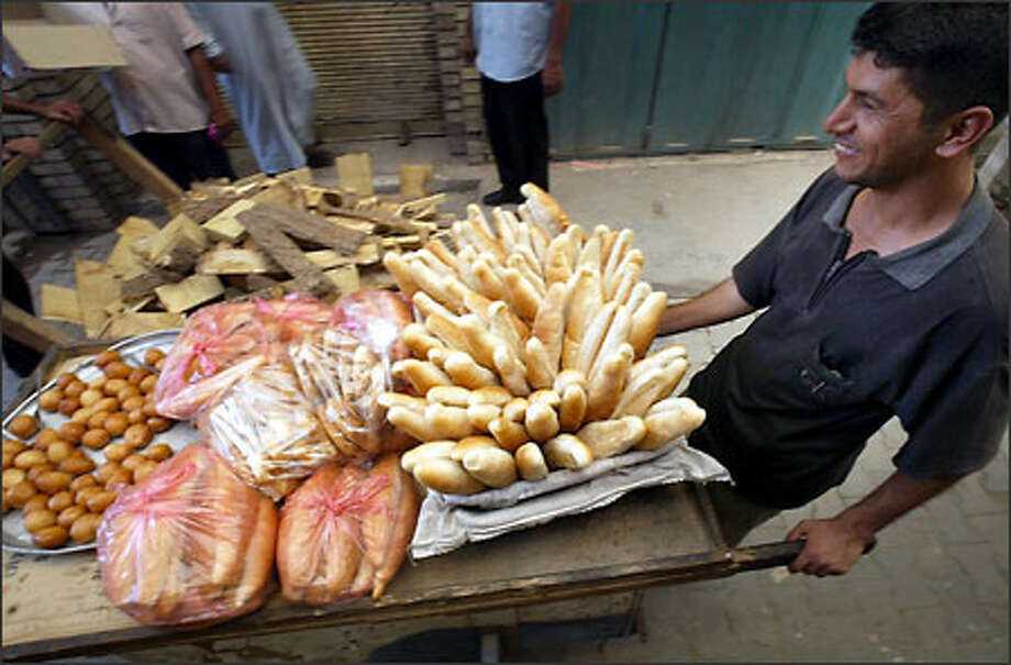 Raheem Sharim pushes a cart of baked goods through a market in the Rasheed district of Baghdad. Sharim, 33, hopes things will get better. Photo: Dan DeLong/Seattle Post-Intelligencer
