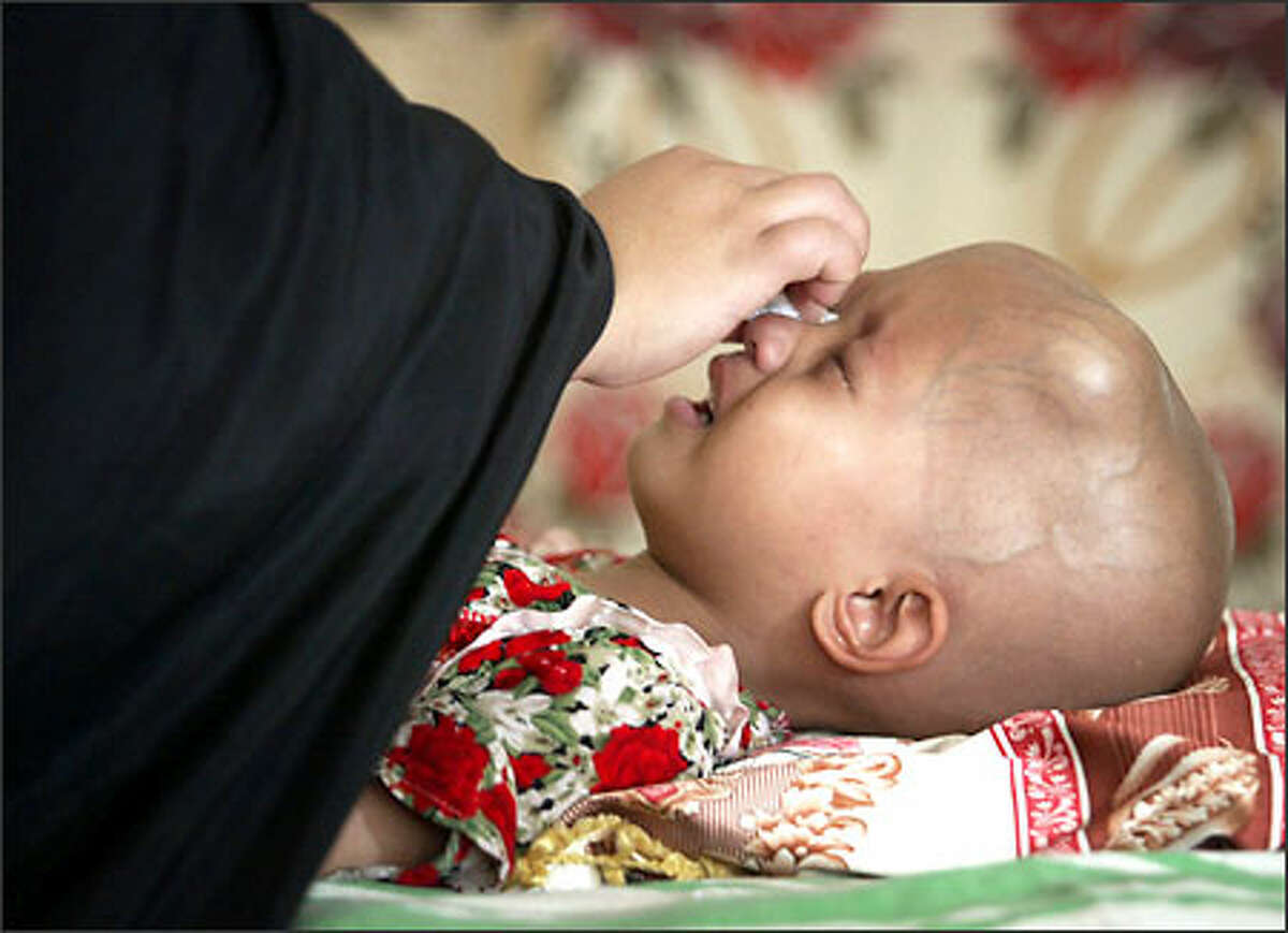 Nakem Faleh wipes tears from the eyes of her 4-year-old daughter, Kasak Hidar, at the cancer ward of the Mother and Child Hospital in Basra, Iraq. Kasak suffers from a neuroblastoma, tumor of the brain. Meanwhile, at least 3,240 civilians have been killed in the Iraq war.