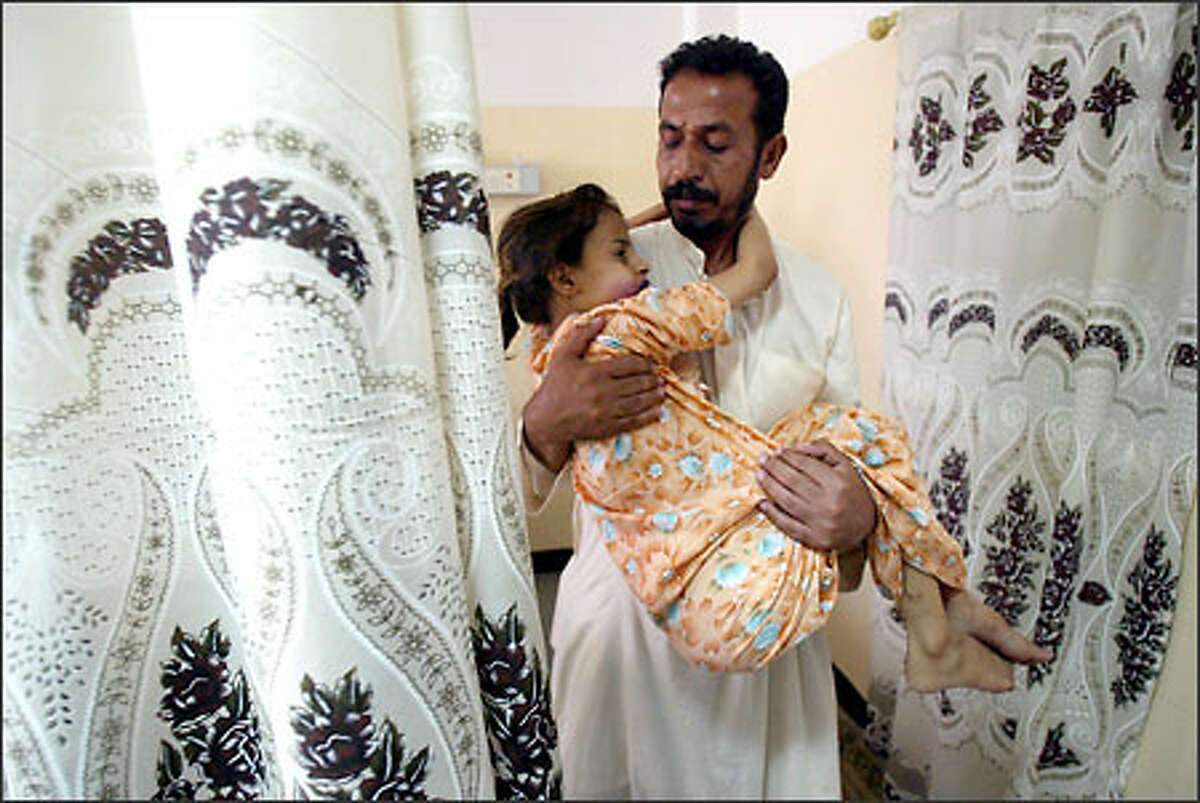 Nine-year-old leukemia patient Ala Hashem is carried from her bed by her father at the Mother and Child Hospital in Basra, Iraq. The hospital is expected to run out of medicine in weeks.