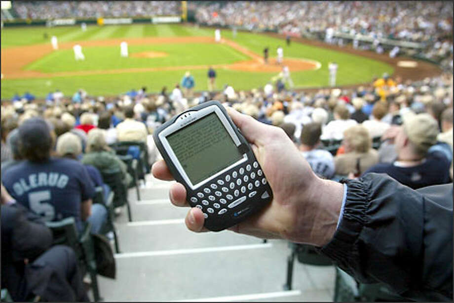 Neil Podmore of the Verrus firm in Vancouver, B.C., shows how a fan at Safeco Field can use a Web-enabled cell phone to order food and beverages. Photo: Gilbert W. Arias/Seattle Post-Intelligencer