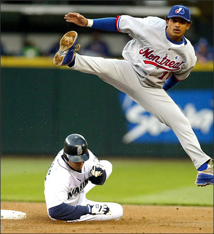 Expos shortstop Orlando Cabrera hurdles John Olerud and makes a throw to first base to complete a second-inning double play last night. Cabrera hit a two-run homer in the third inning. Photo: Karen Ducey/Seattle Post-Intelligencer