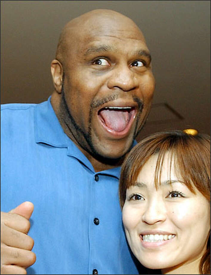 Bob Sapp poses with a Japanese fan for a snapshot. At 25, his NFL career was over and he was broke. He resurfaced as a prizefighter in Japan. Photo: / Associated Press