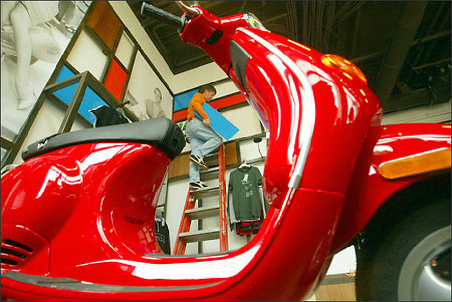 Victor Voris, owner of the new Vespa Seattle boutique, puts up panels in his showroom. The store will open next week. More than 15 million Vespas have been sold worldwide. Photo: Phil H. Webber/Seattle Post-Intelligencer