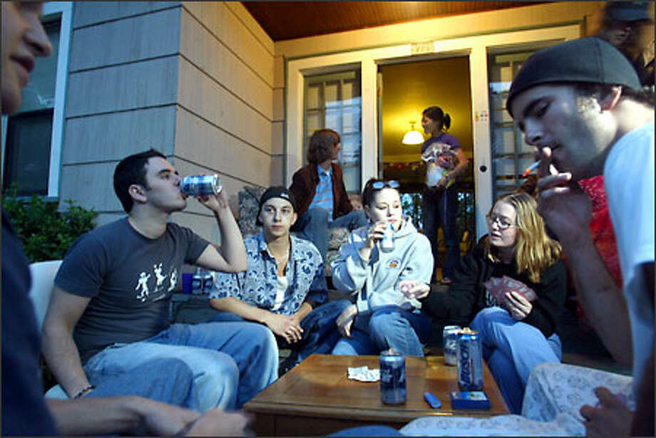Students and friends gather outside a converted single-family house in the University Park neighiborhood of the University District. Photo: Karen Ducey/Seattle Post-Intelligencer