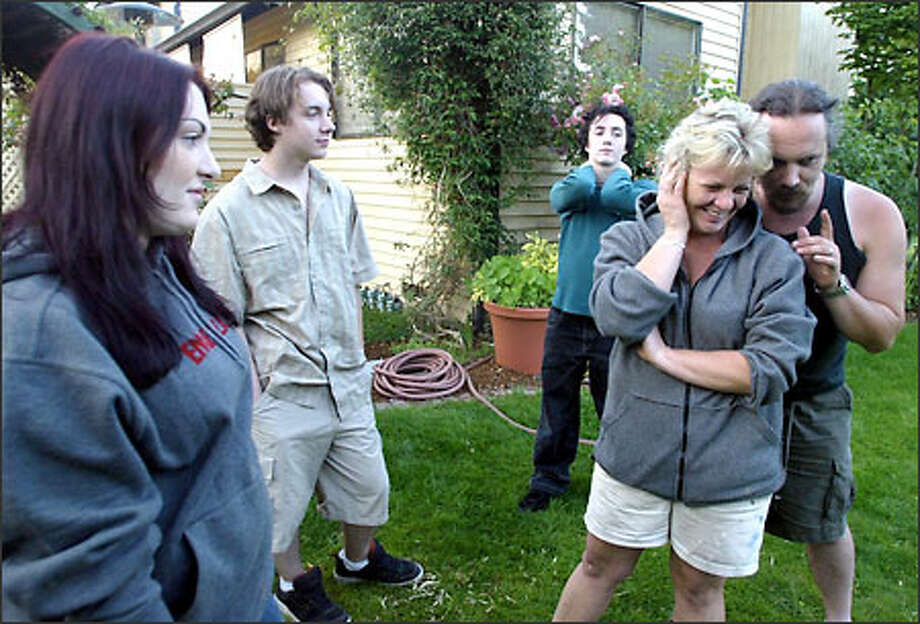 In the yard of their Edmonds home, stay-at-home mom Laurel Dickson jokes with her husband, Edward Dickson, as their three children look on. The kids are, from left to right, Ember, 19, Ian, 17, and 14-year-old Alex. Photo: Gilbert W. Arias/Seattle Post-Intelligencer