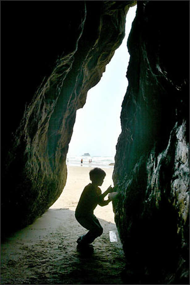 A schoolchild explores a sea cave at Hug Point Recreation Area. Just south of the point is a waterfall and a beautiful golden pocket beach. Photo: Gilbert W. Arias/Seattle Post-Intelligencer