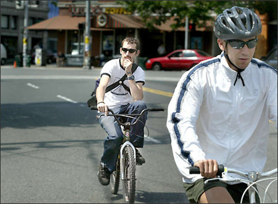 A bicyclist without a helmet, who gave his name as Gold Hick, follows a biker wearing a helmet in Ballard. Hick said he rides without a helmet every day from Beacon Hill to Ballard. Photo: Scott Eklund/Seattle Post-Intelligencer