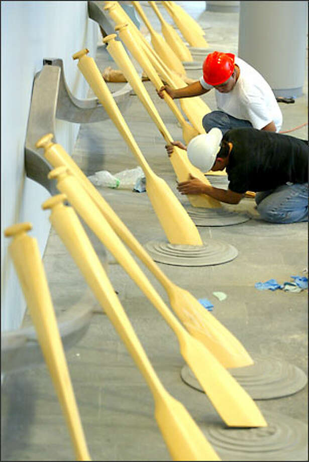 Artist Eric Robertson, front, of British Columbia, and his assistant Oliver Haskell install canoe paddles as part of a larger art installation at Seattle's new City Hall. Mayor Greg Nickels will be the first occupant of the building Monday. Photo: Mike Urban/Seattle Post-Intelligencer