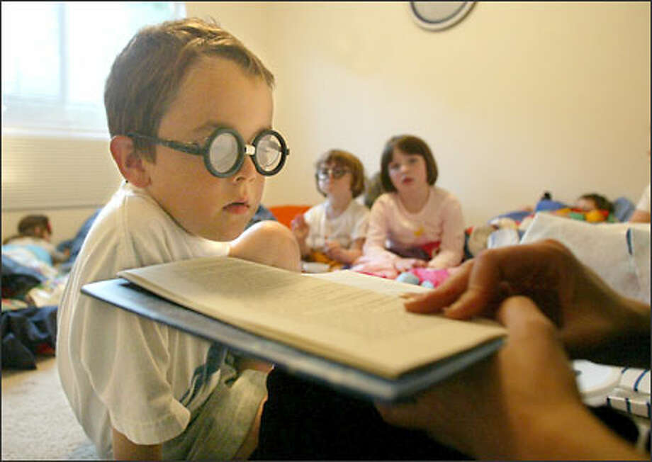 Eli Gee, 6, listens to P-I reporter Kathy George read from the new Harry Potter book at a slumber party while wearing plastic glasses George gave out to all the kids. Photo: Karen Ducey/Seattle Post-Intelligencer