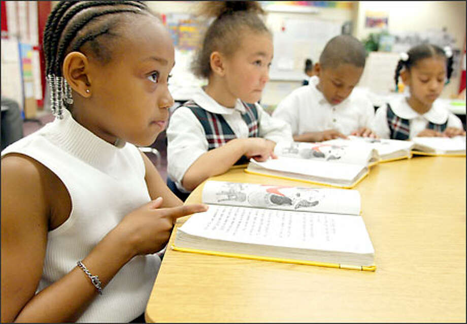 From left to right, African American Academy kindergarten students Zaedrea Robinson, Makeylah Kirkwood, Malik Bundy and Tahjarae Brown read a lesson. Photo: Meryl Schenker/Seattle Post-Intelligencer