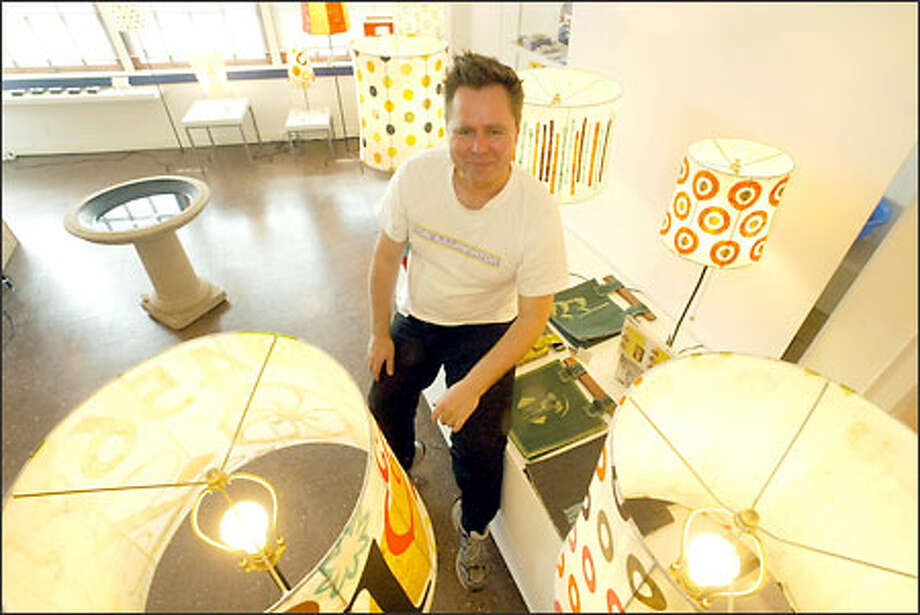 "Misha Neininger, owner of Illuminator 2 Lighting Product & Design, in his shop in the Pike Place Market. ""There's this illumination happening,"" he says. Photo: Phil H. Webber/Seattle Post-Intelligencer"