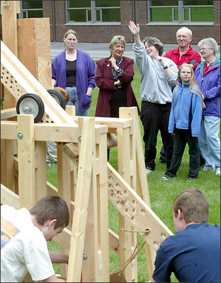 College President Victoria Munoz Richart listens as physics professor Chris Byrne demonstrates how the Trebuchet engine works. Student Jon Padvorac, right, and his brother, a future student, finish up. Photo: Grant M. Haller/Seattle Post-Intelligencer