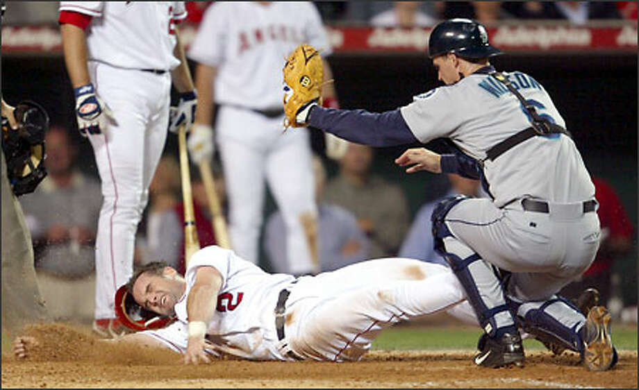 Dan Wilson tags Angels baserunner Adam Kennedy, thrown out by second baseman Bret Boone on the front end of an attempted double steal in the fifth inning. Photo: CHRIS CARLSON/AP
