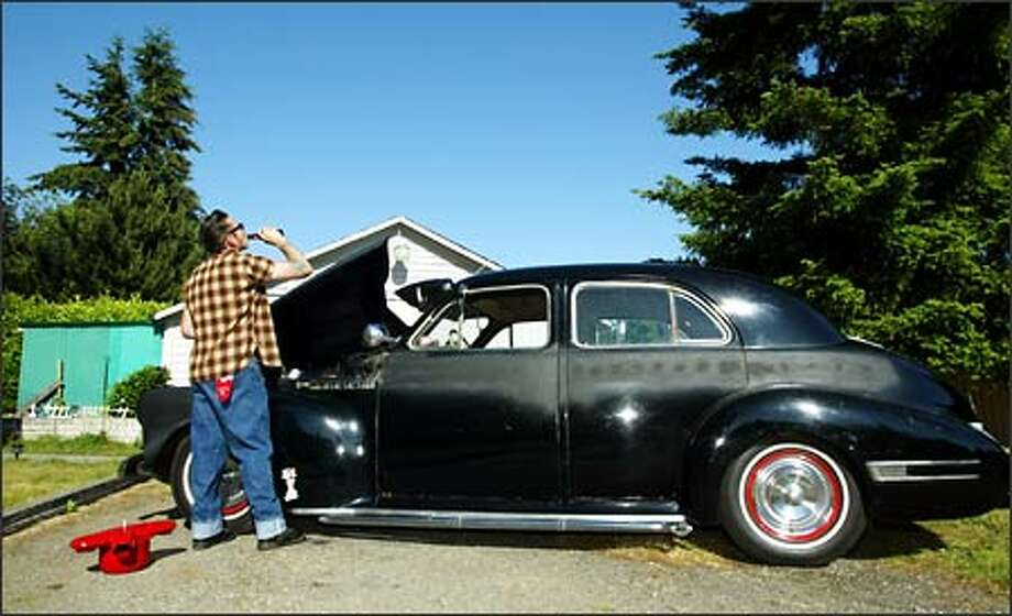 Duke Morris, president of the Rook's Car Club takes a break from working on his 1941 Buick outside his home in Edmonds. Photo: David Bitton/Seattle Post-Intelligencer