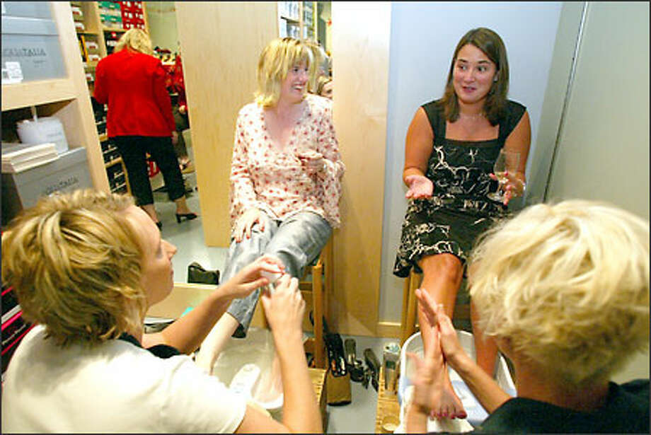 Lisa Amore, top left, tries on shoes while Linda Caudle, middle, and Rebecca Dawson, right, get their feet and legs massaged by Nordstrom's employees Heidi Harris, bottom left and Stacie Witherspoon, bottom right. The free massage was part of a promotion going on at Shoefly shoe store at the north end of Greenlake. The store is hoping that having parties will bring in people that generally wouldn't stop by the store on their own. Photo: David Bitton/Seattle Post-Intelligencer