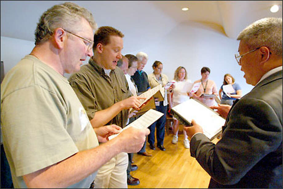 Jim Brauch, left, Trevor Townsend, middle, and Lester Letoto, right, practice with other members of the Thin Blue Line Choir. The group practices Tuesday nights at the Everett Senior Center. Letoto, the choir's director the past two years, says music strikes a positive note for members and with the community. Photo: David Bitton/Seattle Post-Intelligencer