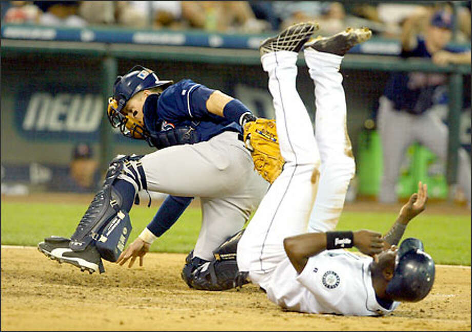 Mark McLemore tumbles after being tagged out by Padres catcher Gary Bennett in the sixth. McLemore tried to score on Dan Wilson's single to center. Photo: David Bitton/Seattle Post-Intelligencer