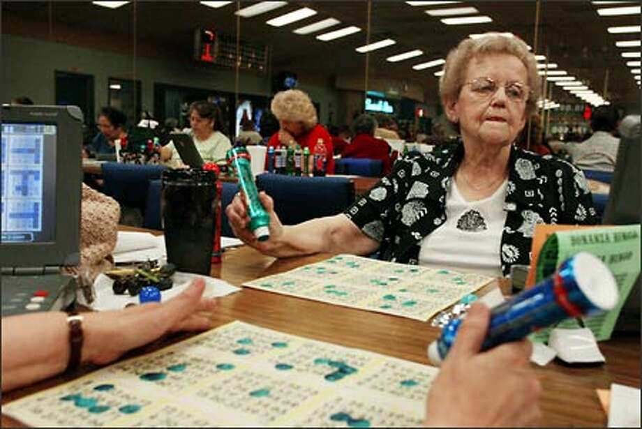 """A bingo player for 25 years, Betty Haugen plays the game six days a week but says she is not addicted. """"I live within my budget and I win enough to play on their money. I play because I don't like to be alone. I have met a lot of people up here that are good friends. I'm known as the cookie lady up here. Doctors recommend us to go to bingo because it is good for our minds."""" Photo: David Bitton/Seattle Post-Intelligencer"""