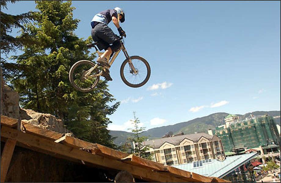 A mountain bike rider catches some air off a jump at the Whistler Mountain Bike Park in Whistler. Whistler Village is in the background. Photo: Jeff Larsen/Seattle Post-Intelligencer