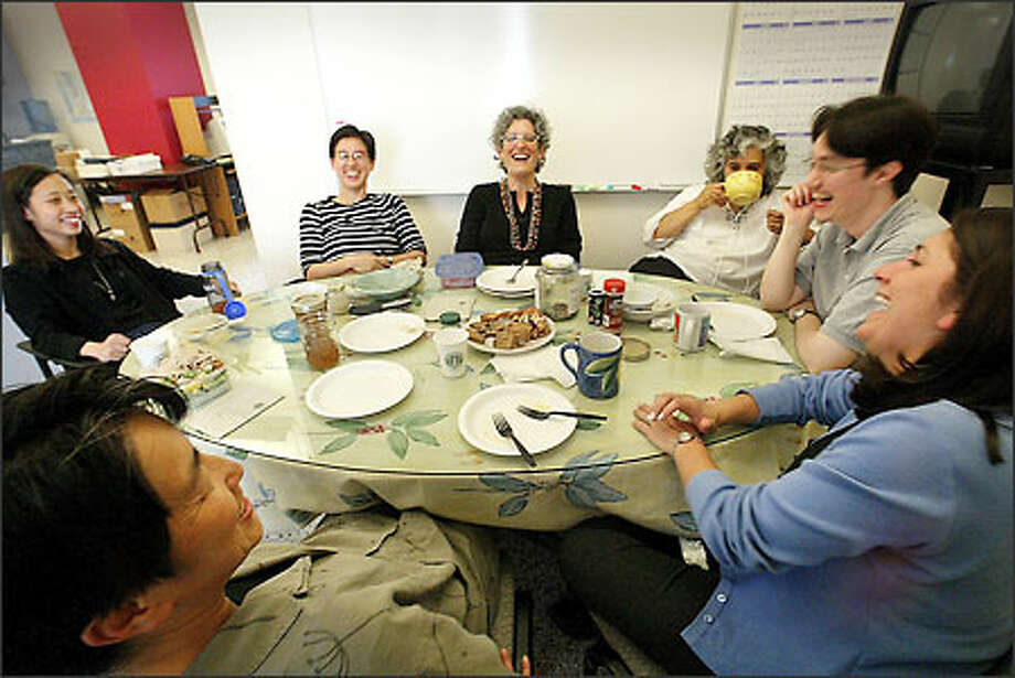 Domestic violence workers enjoy a light moment at the lunch table in their downtown Seattle office. They are (clockwise from bottom left) Nan Stoops, Grace Huang, Judy Chen, Leigh Hofheimer, Lupita Patterson, Christine Olah and Kelly Starr. Photo: Dan DeLong/Seattle Post-Intelligencer